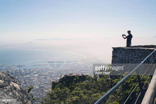 Man taking photo on smartphone from Table Mountain