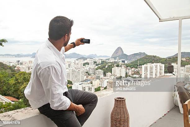 Man taking photo on terrace, Sugarloaf Mountain in background, Riot, Brazil