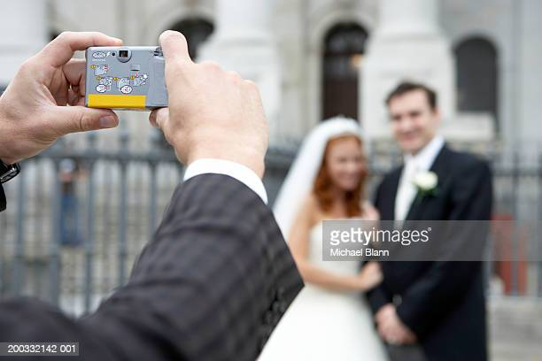 Man taking photograph of bride and groom, close-up