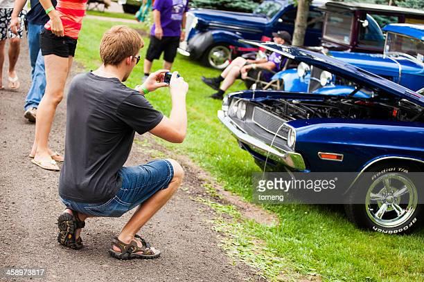 Man Taking Photograph of Classic Car