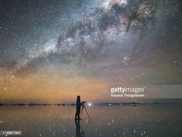 a man taking photograph of dreamlike milky way across salt flat, uyuni, bolivia - ウユニ塩湖 ストックフォトと画像