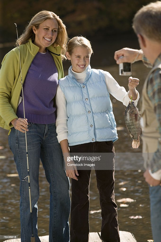 Man taking photograph of mother and daughter fishing : Stockfoto