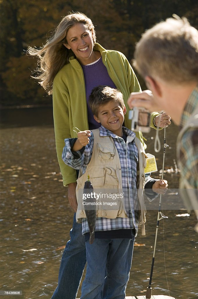 Man taking photograph of mother and son fishing : Stockfoto