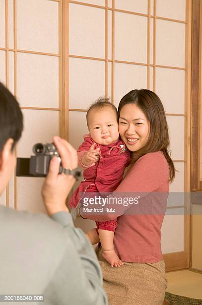 man taking photograph of woman holding baby daughter (9-12 months) - 12 23 months stock pictures, royalty-free photos & images