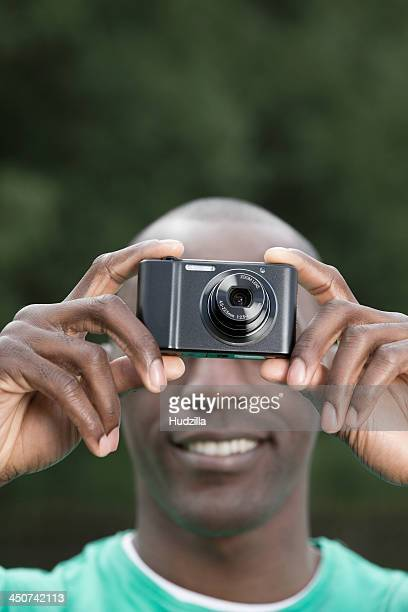 Man taking photograph with digital camera