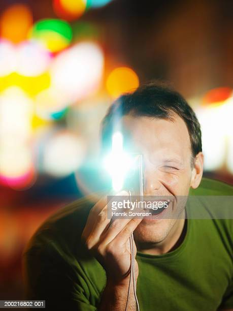 Man taking photograph with flash camera, squinting, close-up