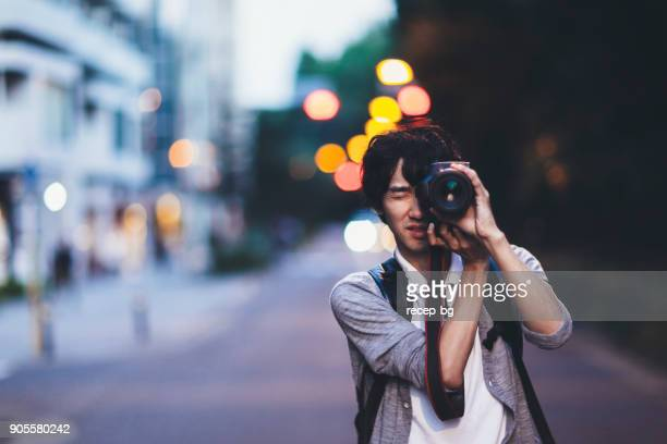 man taking photos at night - photographer stock photos and pictures