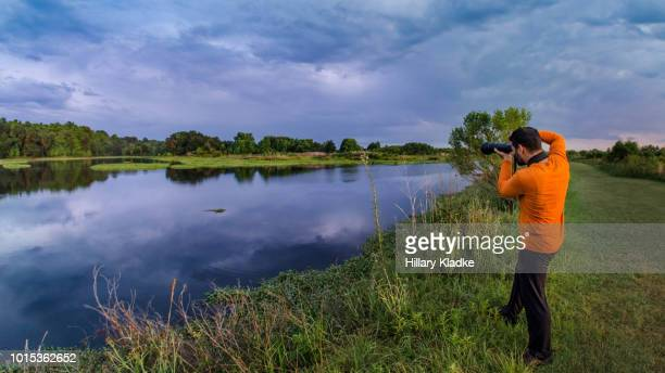 man taking photos of a lake - gainesville florida stock pictures, royalty-free photos & images