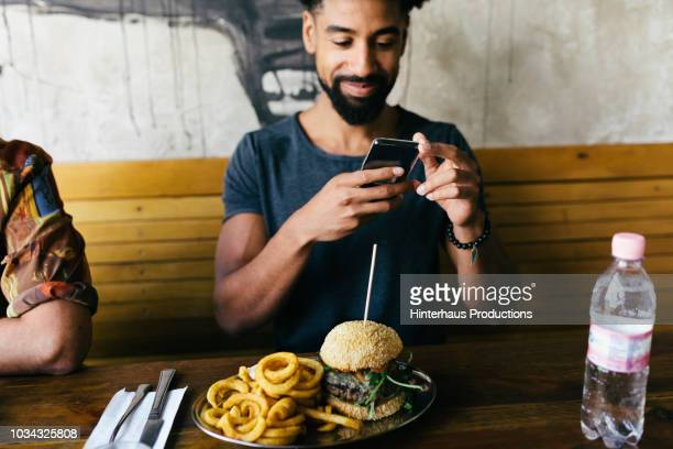 man taking photos of burger with smartphone - generation y stock-fotos und bilder