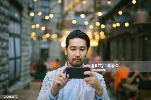 man taking photos with smartphone - photo messaging stock pictures, royalty-free photos & images