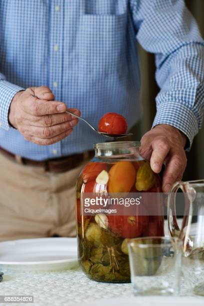 man taking pickles out for taste - cliqueimages stock pictures, royalty-free photos & images