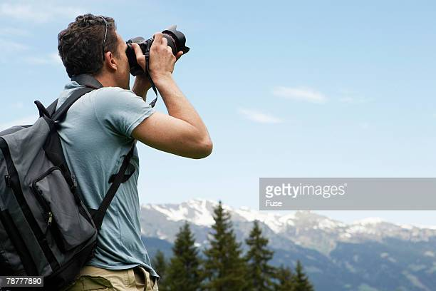 Man Taking Picture in Mountain Landscape