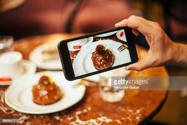 Man taking picture of a chocolate cake on a table in a cafe with his smart phone