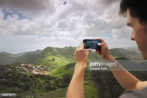 Man taking picture of beautiful landscape with sma