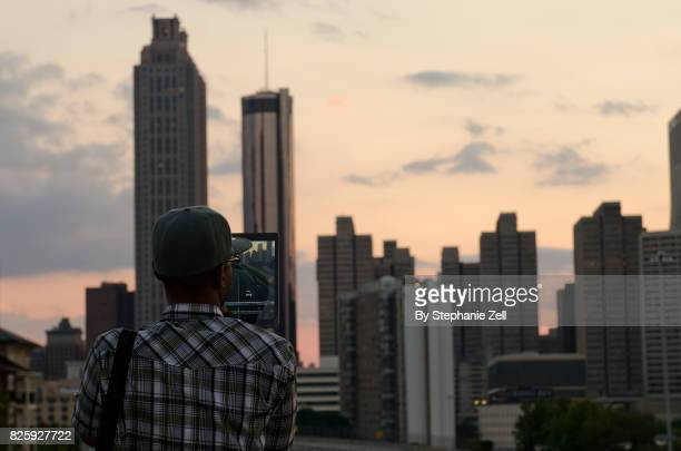 Man taking picture of city skyline at sunset on a tablet computer