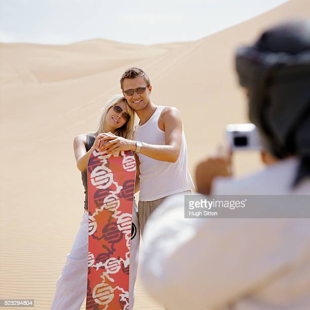 man taking picture of couple holding snowboard - hugh sitton stock pictures, royalty-free photos & images