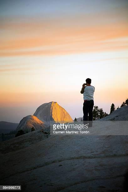 Man taking picture of Half Dome, Yosemite.