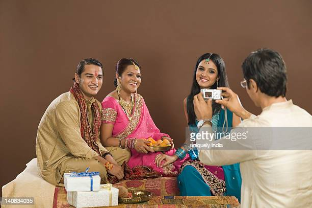 Man taking picture of his family with a digital camera