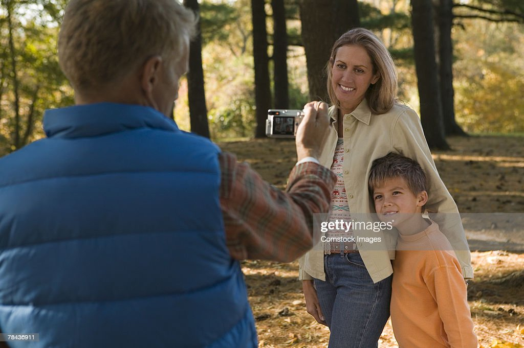 Man taking picture of mother and son outdoor : Stockfoto