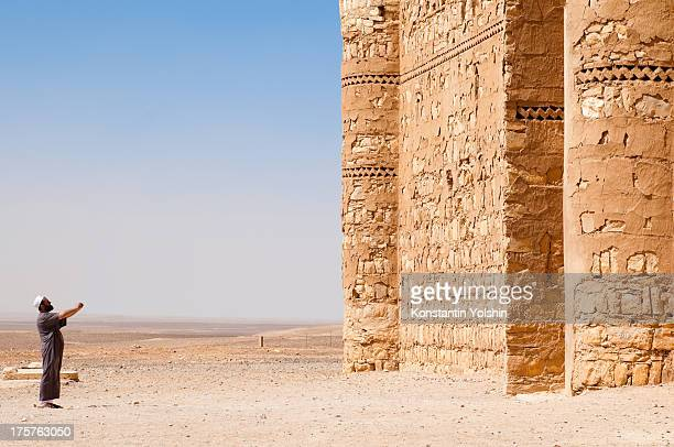 Man taking picture of Qasr Kharana, one of Jordan's desert castles. October 2009, Jordan.
