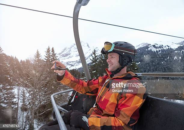 Man taking picture of self on ski lift.