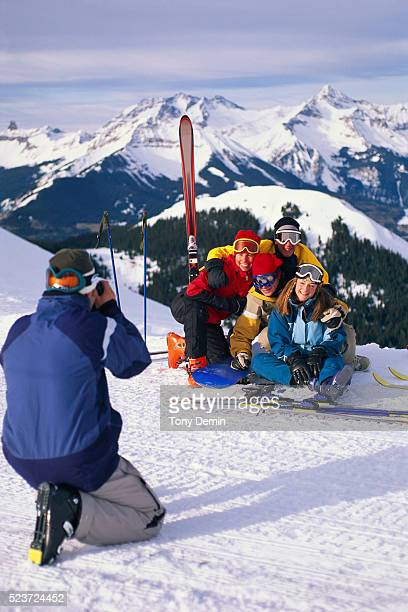 Man Taking Picture of Smiling Skiers Sitting on Mountain