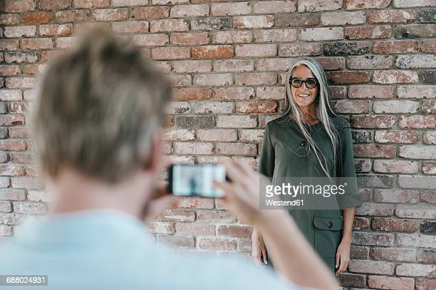 Man taking picture of smiling woman with long grey hair at brick wall
