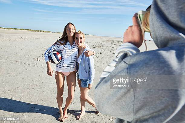 Man taking picture of two friends with beach volleyball on the beach