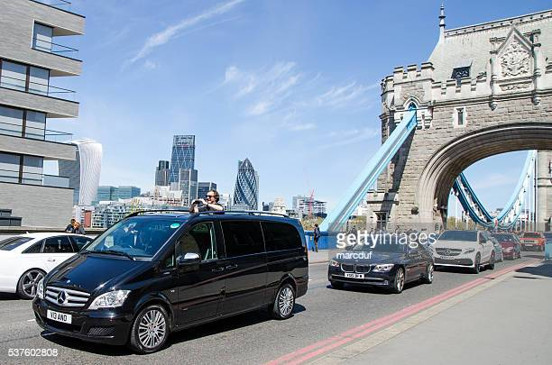 Man taking picture out of roof car on Tower Bridge