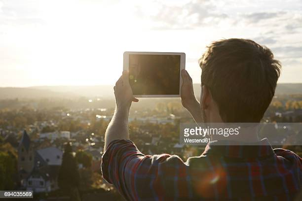Man taking picture with a tablet on a hill above a town