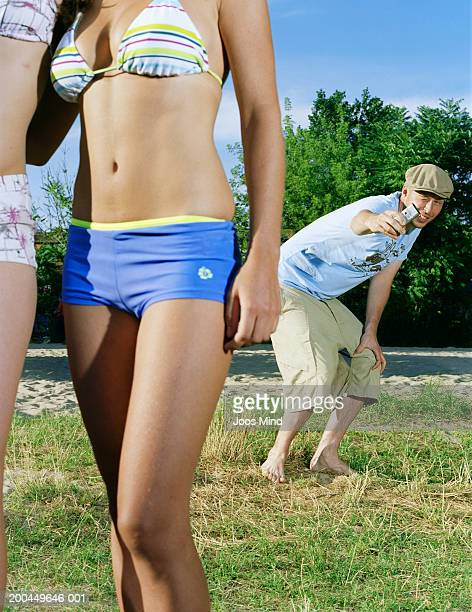 Man taking picture with camera phone of women in bikinis, close-up