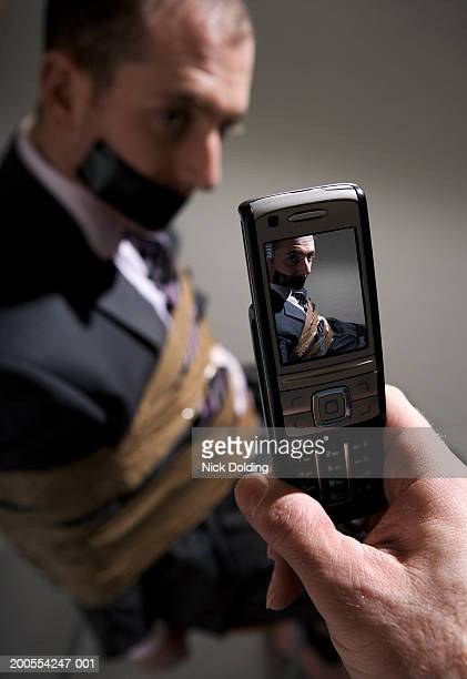 man taking picture with mobile phone of tied up businessman - man tied to chair stock photos and pictures