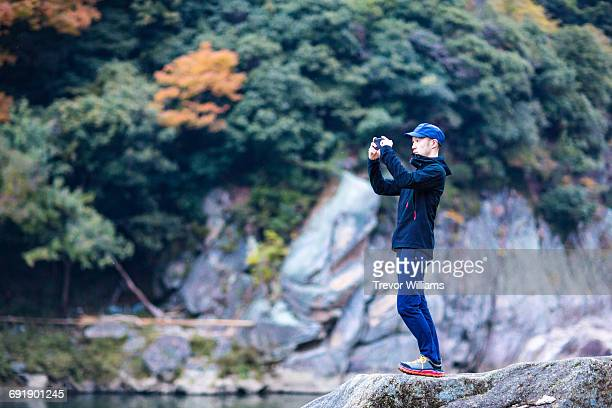 man taking picture with smartphone in the forest - capturing an image stock pictures, royalty-free photos & images