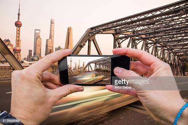 Man taking pictures from personal point of view with smartphone of the Shanghai cityscape from the Waibaidu bridge with car in motion.