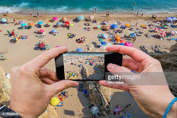 Man taking pictures from personal point of view with smartphone of the colorful beach from above in the Mediterranean sea.