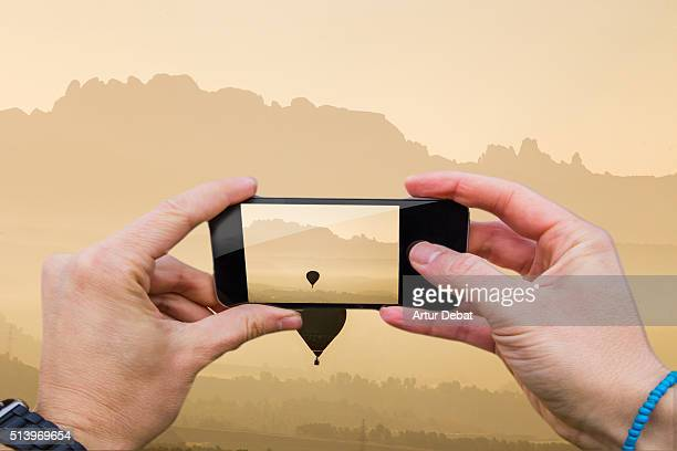Man taking pictures from personal point of view with smartphone of the hot air balloon reunion flying in the Catalonia region on sunrise.