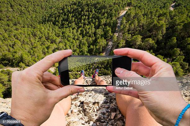Man taking pictures from personal point of view with smartphone of the landscape from above the cliff edge with nice view.
