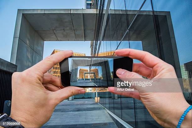 Man taking pictures from personal point of view with smartphone of the Barcelona business district cityscape with modern architecture.