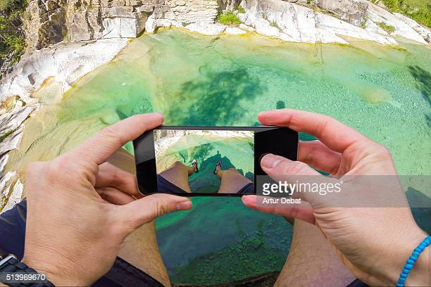 Man taking pictures from personal point of view with smartphone of the green creek in the Catalan Pyrenees cooling off in summer time.
