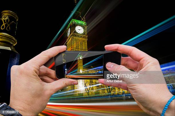 Man taking pictures from personal point of view with smartphone of the London cityscape at night with the Big Ben and light trails.