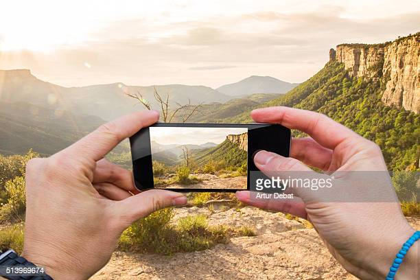 Man taking pictures from personal point of view with smartphone of teh stunning landscape on sunrise with beautiful valley and crags.