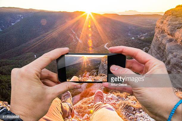 Man taking pictures from personal point of view with smartphone of the stunning landscape on sunset in the Catalan Pyrenees.