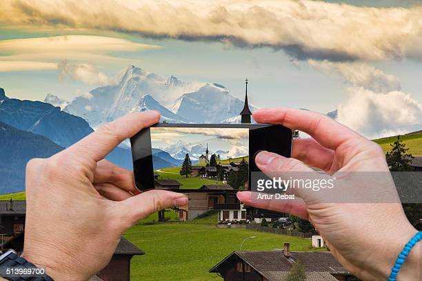Man taking pictures from personal point of view with smartphone of the Switzerland landscape with church and the snowy Alps on the background.