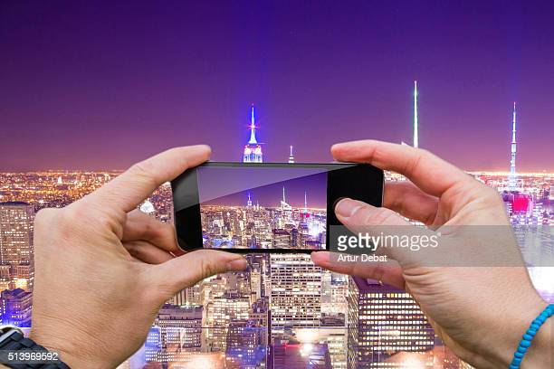 Man taking pictures from personal point of view with smartphone on top of New York city with Empire State at night.