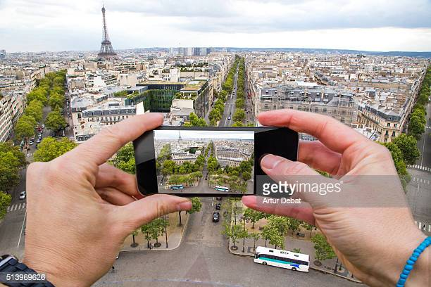 Man taking pictures from personal point of view with smartphone on top of Paris city with Tour Eiffel skyline.