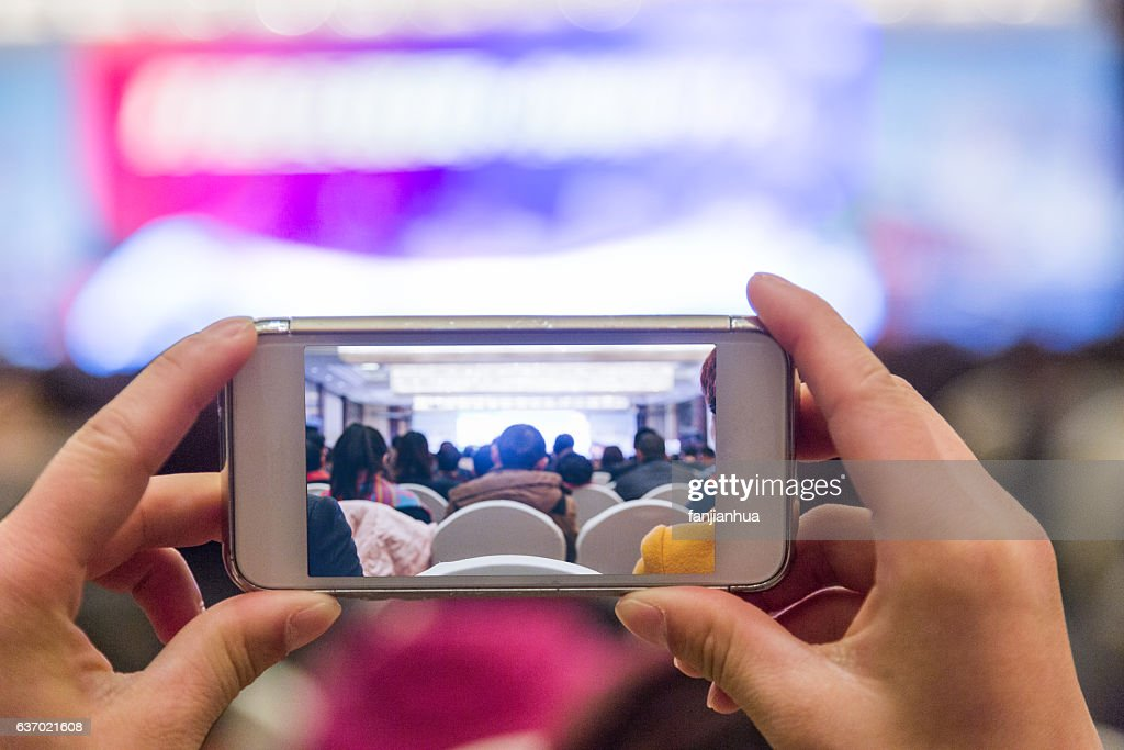 man taking pictures in an auditorium : Stock Photo
