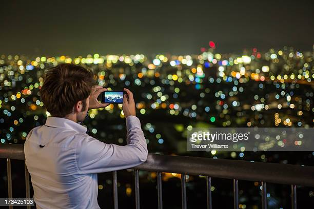 man taking pictures of city lights with a smartpho