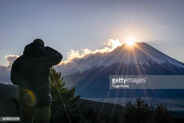 a man taking pictures of dimond fuji from nijumagari pass in oshino - ダイヤモンド富士 ストックフォトと画像
