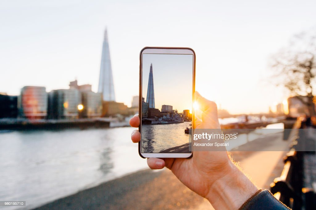 Man taking pictures of London skyline with his smartphone, personal perspective view : Stock Photo