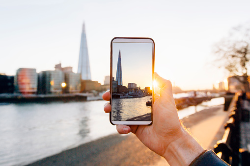 Man taking pictures of London skyline with his smartphone, personal perspective view - gettyimageskorea